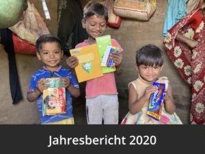 Zwei Jungen und ein kleines Mädchen lächeln. Sie stehen in ihrem Zuhause und haben Lehrmittel und, Schokolade und Stifte in den Händen. Diese wurden im Rahmen der Corona Nothilfe von Mudita School, dem Projekt von Bharat Wankhade aus Indien, verteilt.